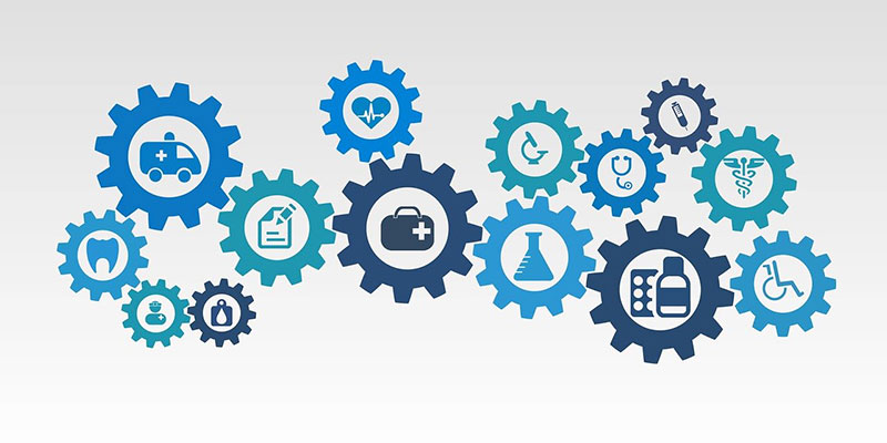 Various cogs with icons related to health and social care within